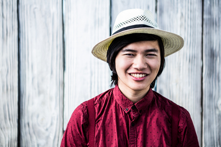 straw the hat: Smiling hipster with a straw hat on wooden background Stock Photo