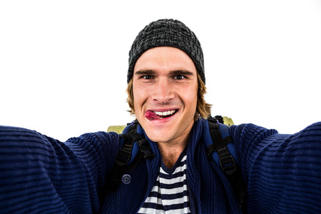 Backpacker holding the camera and grimacing on white screen Stock Photo