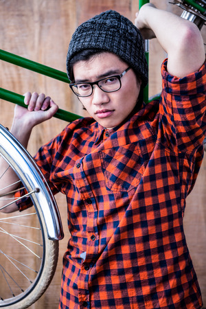carrying: Hipster carrying a bike on his shoulders on wooden background