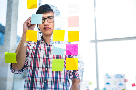 sticky notes: Creative businessman writing on sticky notes in office Stock Photo