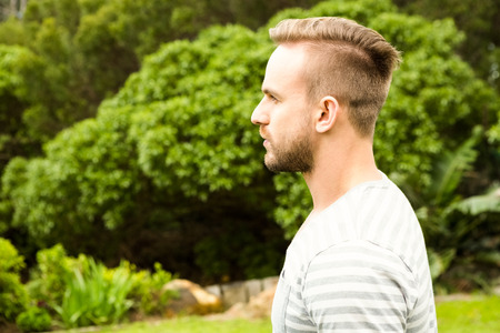 unsmiling: Side view of unsmiling man in the garden Stock Photo