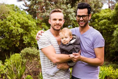 Glimlachend echtpaar met kind in de tuin