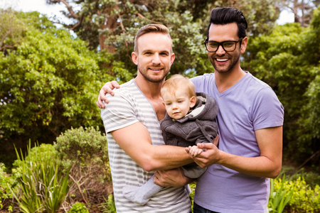 young adult men: Smiling  couple with child in garden