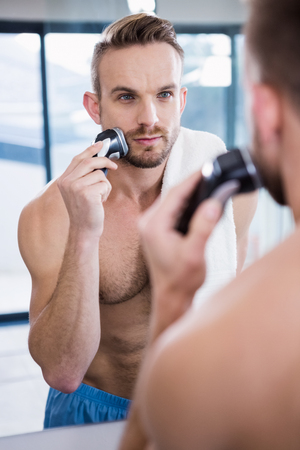 personal grooming: Concentrated man shaving his beard in bathroom Stock Photo