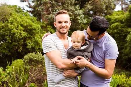 homosexual: Sonriente pareja de homosexuales con el niño en el jardín