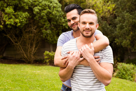 Smiling gay couple hugging in garden Stock Photo