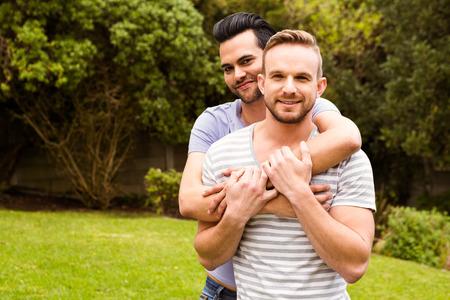 Sourire couple gay étreindre dans le jardin