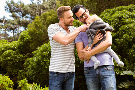 Smiling gay couple with child in garden