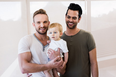 homely: Smiling gay couple with child at home