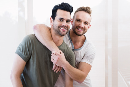 Smiling gay couple hugging at home