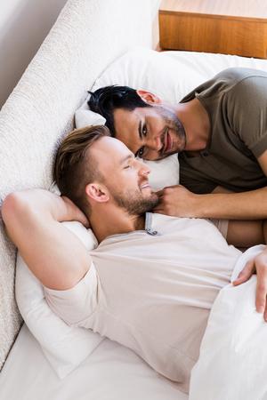 couple bed: Heureux couple gay couché sur le lit à la maison