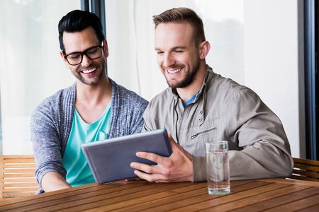 hombres gays: Sonriente pareja de homosexuales que usa la tablilla al aire libre