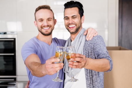 unpacking: Smiling gay couple toasting with champagne while unpacking cardboard