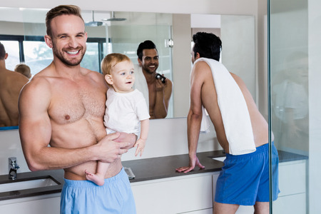 personal grooming: Smiling gay couple with child in the bathroom