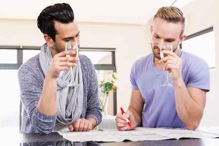encircling: Smiling gay couple surrounding ads in the newspapers