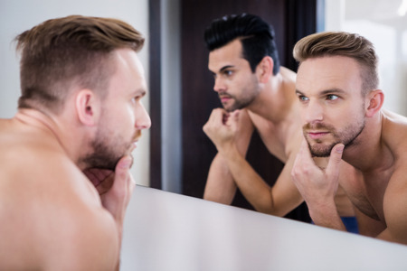 personal grooming: Unsmiling men in front of mirror in the bathroom
