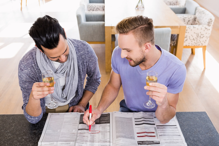 triumphing: Smiling gay couple surrounding ads in the newspapers
