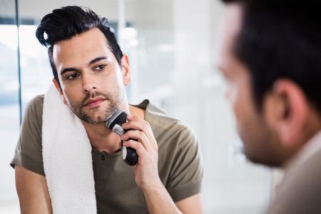 electric razor: Handsome man using electric razor in the bathroom