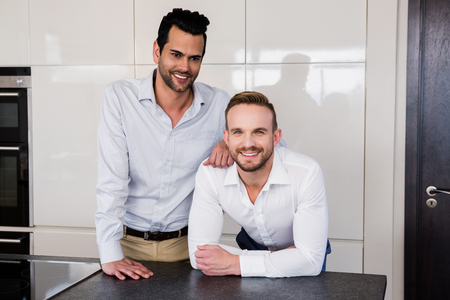 Smiling gay couple in the kitchen at home