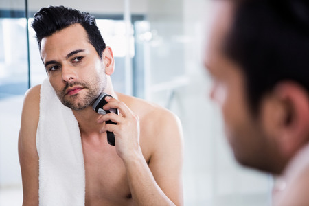 personal grooming: Handsome man shaving in the mirror in the bathroom