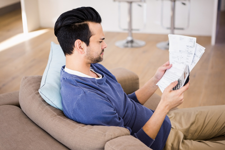 figuring: Serious man checking receipts at home