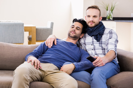 couple on couch: Gay couple watching television on the couch
