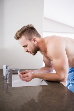 personal grooming: Handsome man drinking water from the sink in the bathroom