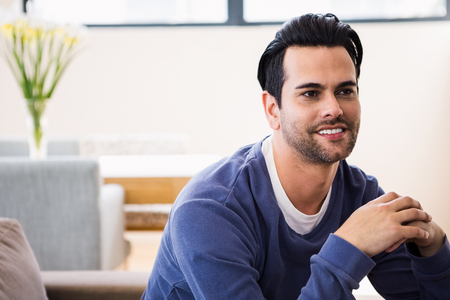 day dreaming: Handsome man day dreaming on the couch in living room