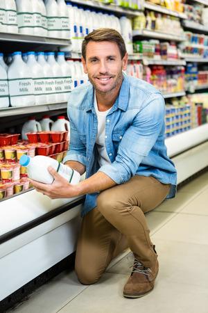 Bell'uomo leggere gli ingredienti in una bottiglia di latte al supermercato Archivio Fotografico