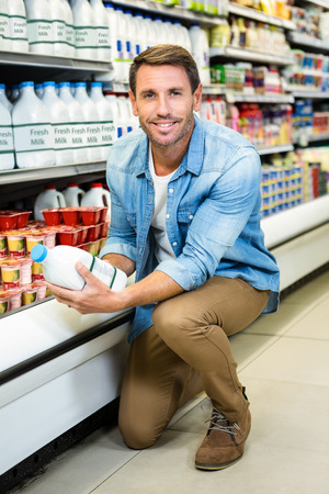 crouched: Handsome man reading the ingredients on a milk bottle at the grocery store Stock Photo