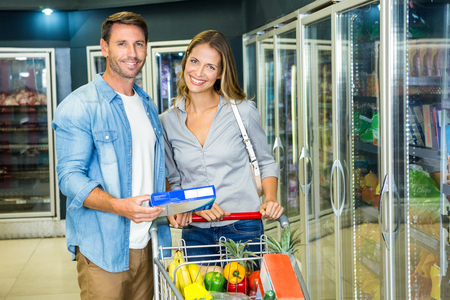 alimentos congelados: Happy couple buying frozen food at the grocery store