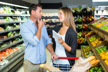 dudando: Cute couple doing grocery shopping together at the supermarket