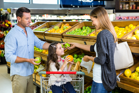 family with one child: Cute family choosing groceries together in the supermarket