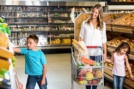 young adults: Happy family doing shopping in grocery store