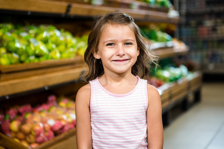 Portrait of smiling little girl in grocery store