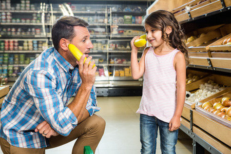 groceries: Father and daughter playing with bananas in grocery store
