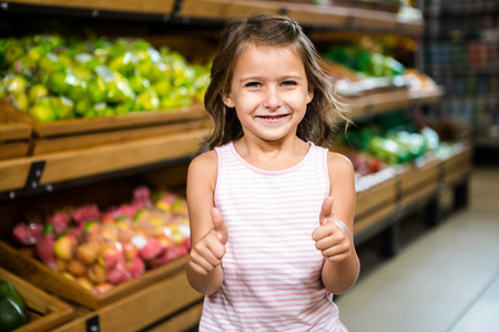 thumps up: Portrait of little girl with thumps up in grocery store