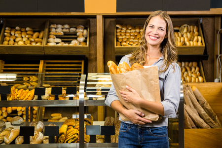Portrait of woman holding paper bag in grocery store Stock Photo