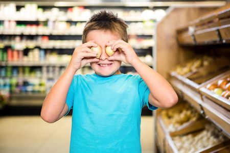 playing the market: Little boy playing with products in grocery store Stock Photo