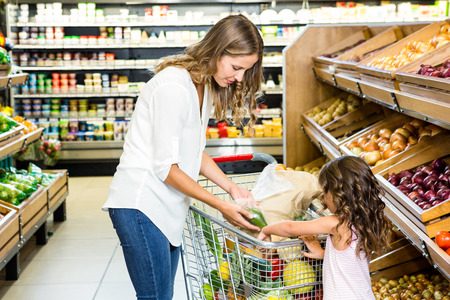 grocery shelves: Mother and daughter doing shopping in grocery store