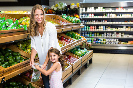 grocery store: Mother and daughter doing shopping in grocery store