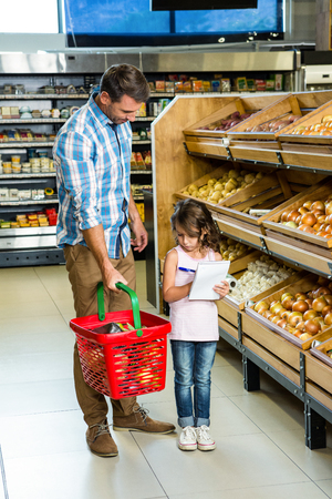 grocery baskets: Father and daughter doing shopping in grocery store