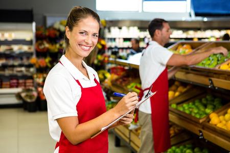 abarrotes: el personal de tienda de comestibles con el portapapeles en un colmado