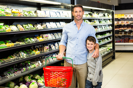 grocery shelves: Father and son at the grocery store smiling at the camera