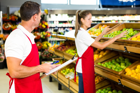 store: Grocery store staff with clipboard in grocery store Stock Photo