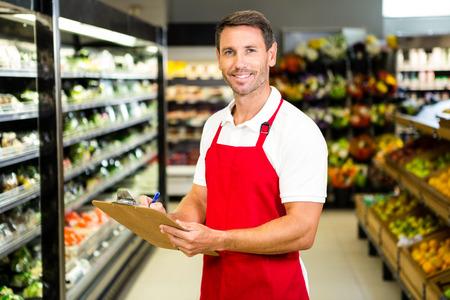 Uśmiechnięty pracownik ze schowkiem w sklepie spożywczym