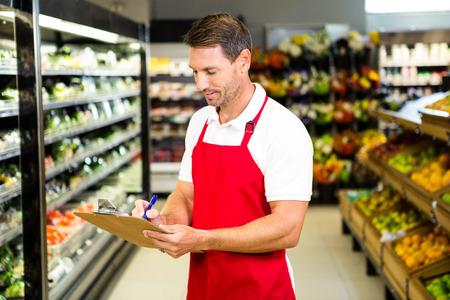 abarrotes: Trabajador sonriente con el sujetapapeles en la tienda de comestibles Foto de archivo