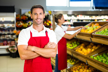 co worker: Smiling worker in front of colleague in grocery store