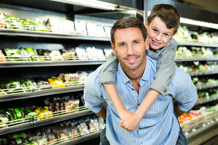 grocery store: Father giving son a piggy back in grocery store