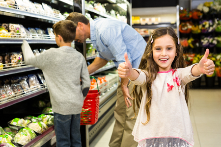 thumps up: Smiling daughter with thumps up in grocery store